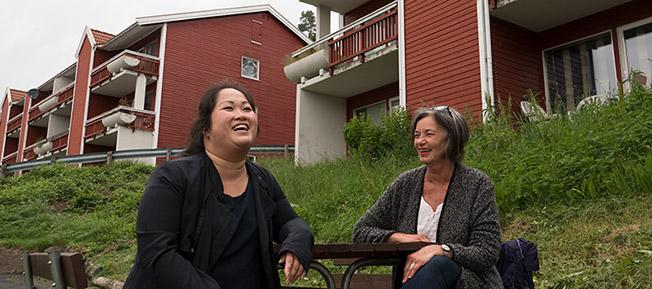 Bilde av Nhung Nguyen og Trine Dønhaug foran de 67 leilighetene i boligstoftelsen.